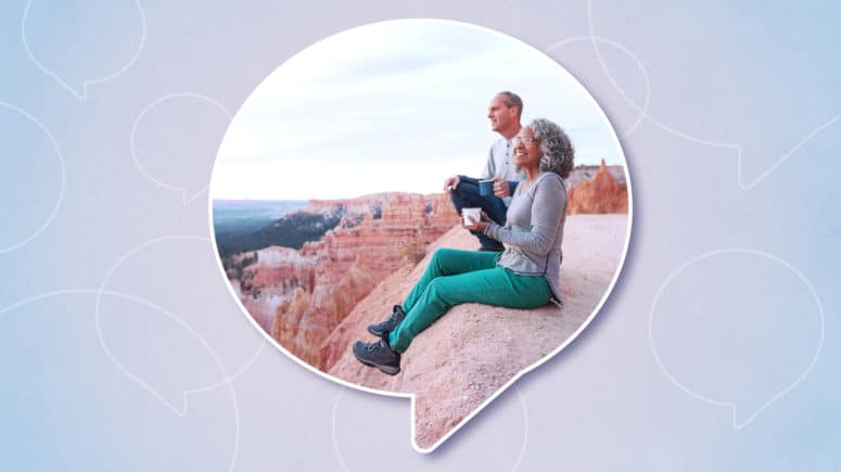 An active senior couple sitting on the edge of a canyon, enjoying the view