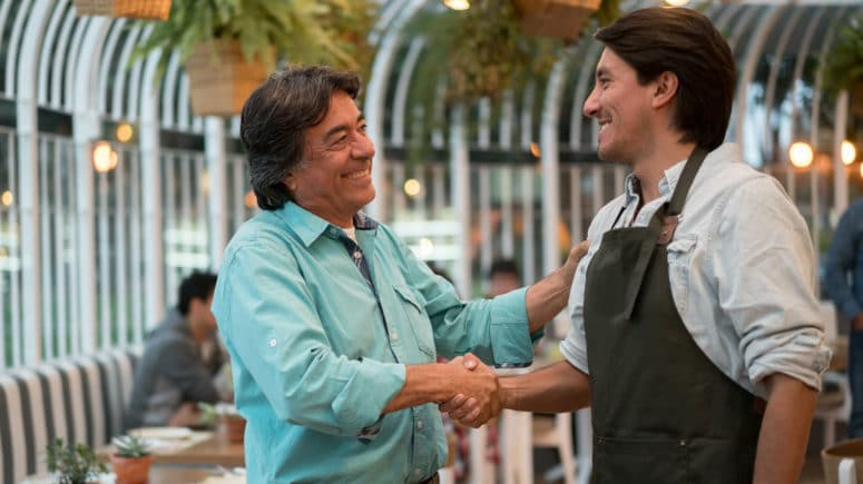 Father and son shake hands in their family owned restaurant.
