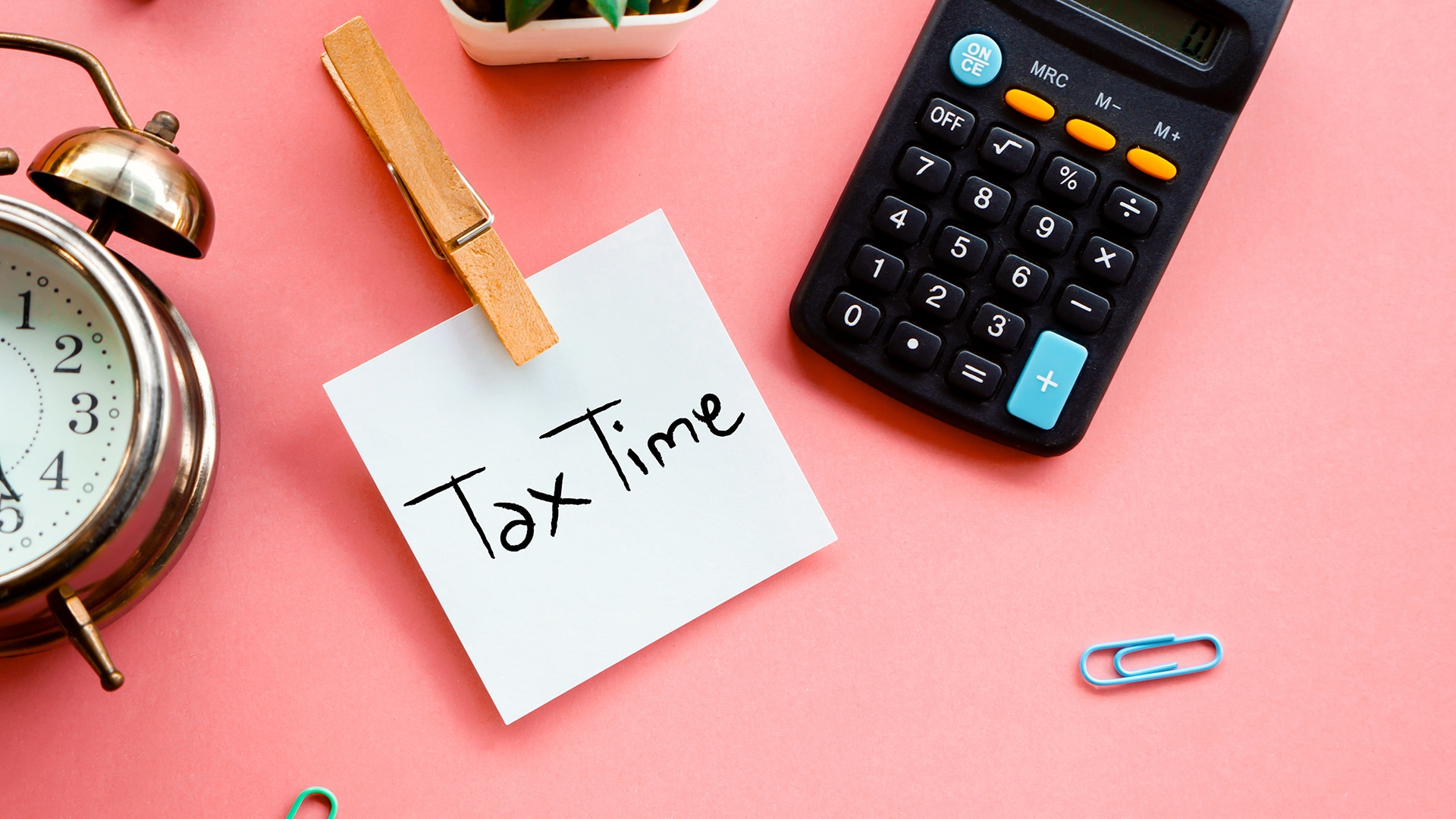 """Clock, calculator and post-it note reading """"Tax Time"""" on a desk."""