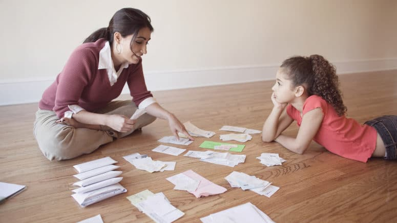 A mother speaks with her daughter while sitting on the floor. Financial papers spread on the floor between them.