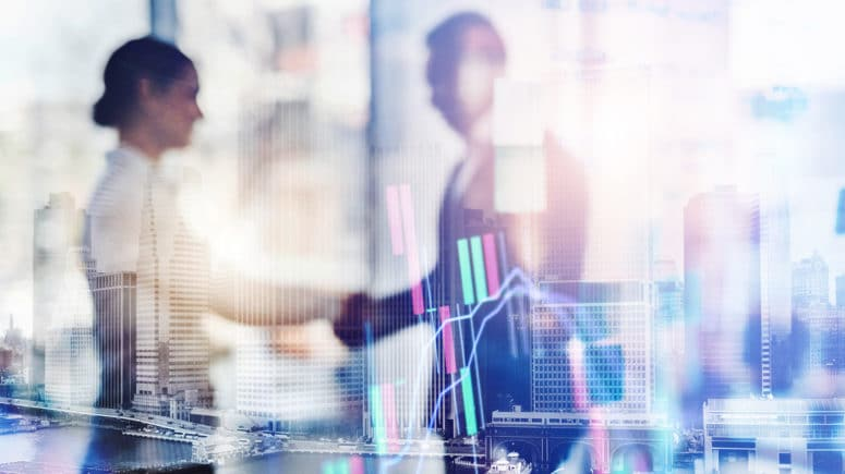 Out of focus image of a businessman and business woman shaking hands, with superimposed skyscrapers and market charts.