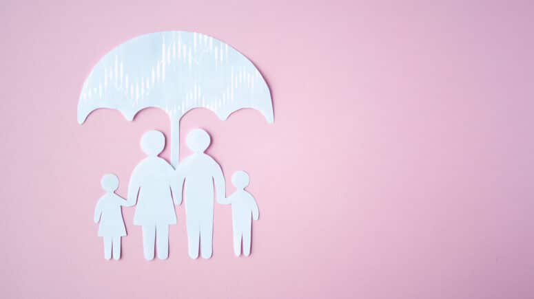 Paper cut out of a family under an umbrella on a pink background. Stock market charts can be seen in the umbrella.